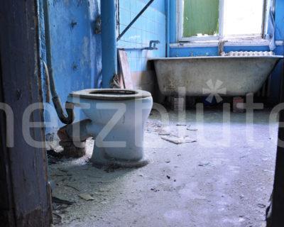 Ein altes blaues Badezimmer in einer DDR Kaserne zerfällt im Laufe der Zeit zu Staub, Lost Places, Rotten Places nahe Berlin. EIne Badewanne steht im Hintergrund.