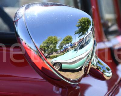 Die gebogene Rückseite eines verchromten Außenspiegels an einem roten Oldtimer zeigt das Spiegelbild eines mintfarbenen weiteren Oldtimers. Das Spiegelbild gibt es hier doppelt. Es entsteht ebenfalls an der Halterung des Spiegels.