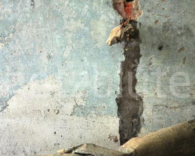 Stromausfall bildlich dargestellt. Eine Steckdose ist aus der Wand gefallen und hängt noch am Kabel. Am Boden liegt eine alte Prawda. Fotografiert in einer Ruine.