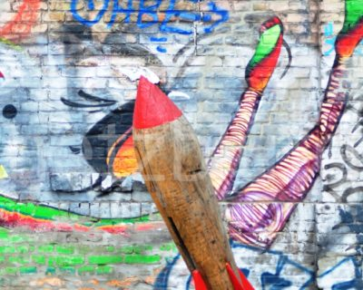 Street Art in Berlin, eine kleine Rakete aus Holz steht vor einer Mauer mit buntem Graffiti. Auf zum Mond geht es hier nur für Gartenzwerge und andere Kleinstlebewesen.