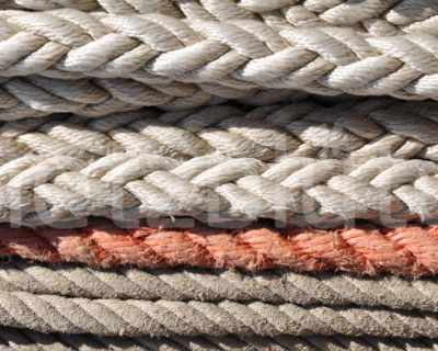 Seile liegen ordentlich zu einem Stapel gelegt, auf einem Boot. Sie sind quasi aufgetaut.