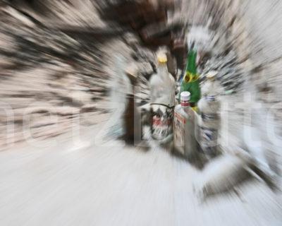 Schnapsflaschen bilden einen Anziehungspunkt, der mit Warp Effekt dargestellt ist. Alkohol verursacht Sucht und Durcheinander in unserem Leben. Beklemmendes Foto von einem Drehmoment.