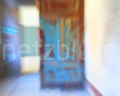 Eine alte Tür im Flur einer Ruine zeigt nur noch wenig blaue Farbe. Der Warp Effekt macht die Tür zur Schwebetür, der sich der Betrachter des Bildes zu nähern scheint.