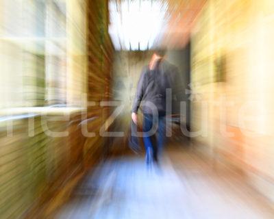 Ein Geist läuft den langen Flur im Geisterhaus entlang. Der Warp Effekt saugt scheinbar den gesamten Raum am Ende des Flurs ein. Der abgebildete Mensch verschwimmt und wird ebenfalls ins Zentrum gezogen. Er sieht aus wie ein Geist.